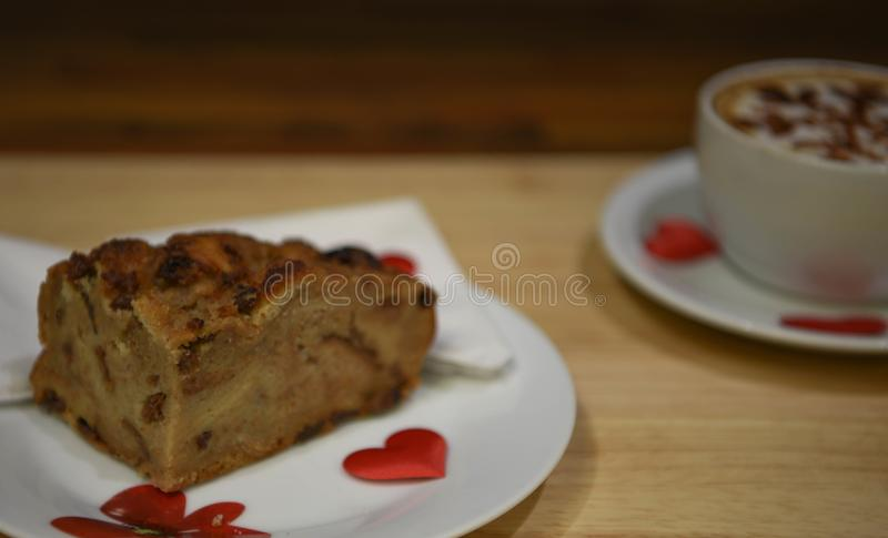 Macro close up food photography of homemade bread and butter pudding with red love heart decorations and coffee cup in background royalty free stock photo