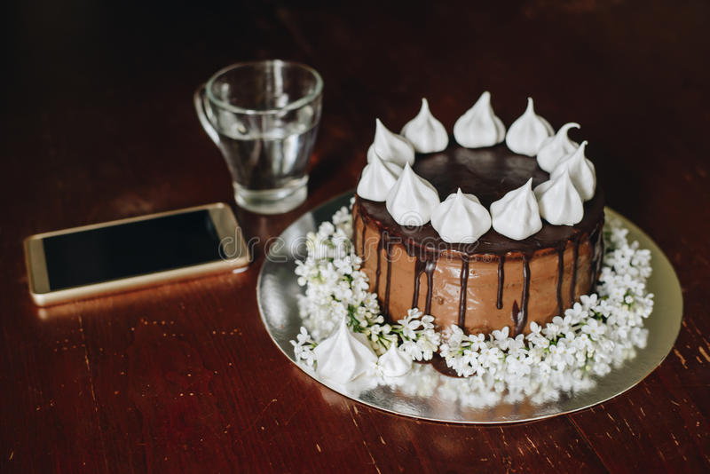 Home made cake with glass of water and phone. On wooden table royalty free stock photography