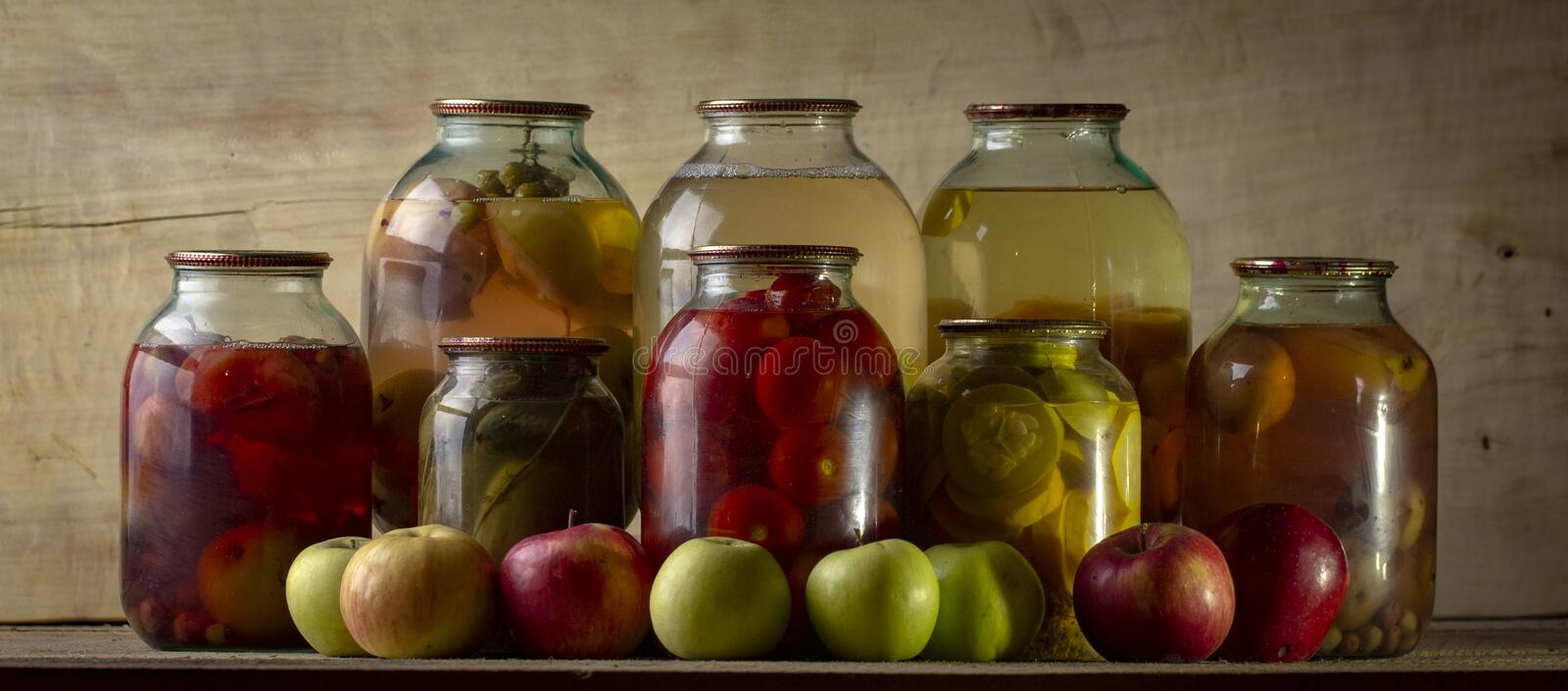 Home-made canned compote and fresh fruit on the basement shelf still life royalty free stock photos
