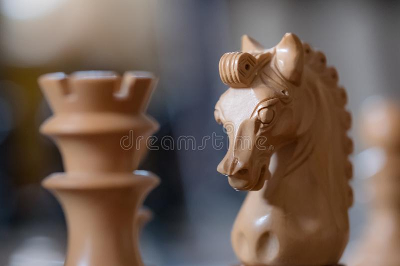 Close-up of a hand carved, wooden chess piece seen next to an out of focus rook. royalty free stock photo