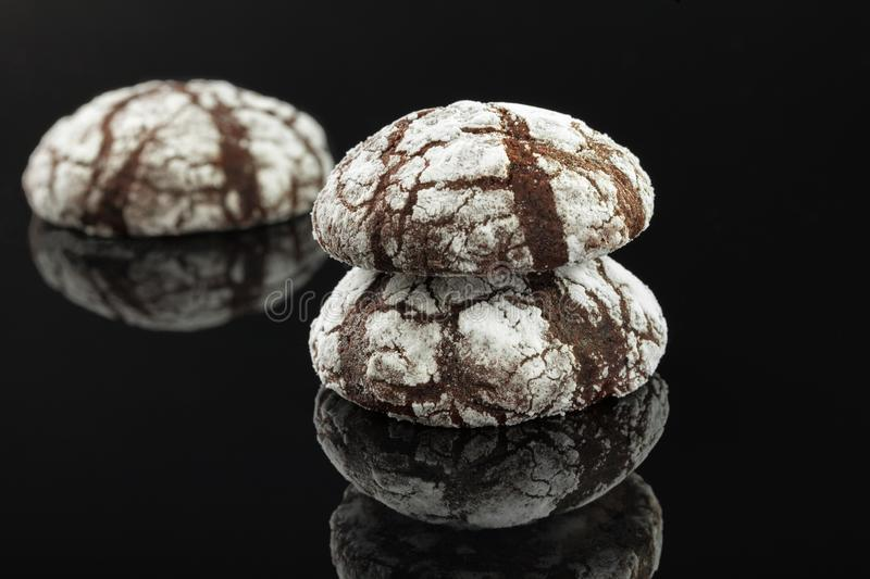 Home made chocolate chip cookies with cracks. Covered with white powdered sugar. On a black background royalty free stock photos