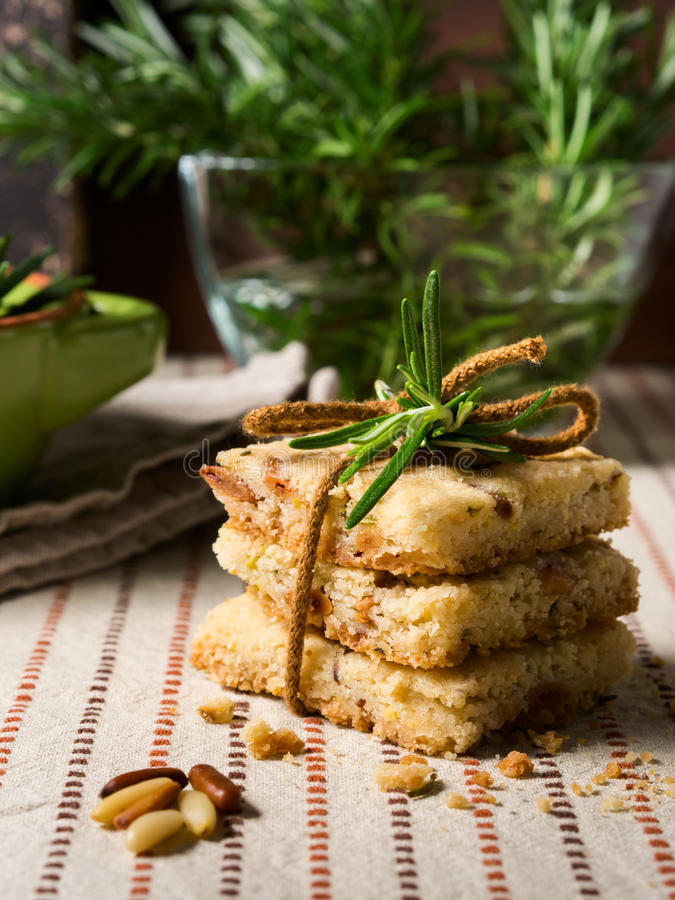 Home made cookies with rosemary and pignoli nuts. Home made butter cookies with rosemary, pignoli and pistachio nuts on table cloth with rosemary sprigs in the stock photo