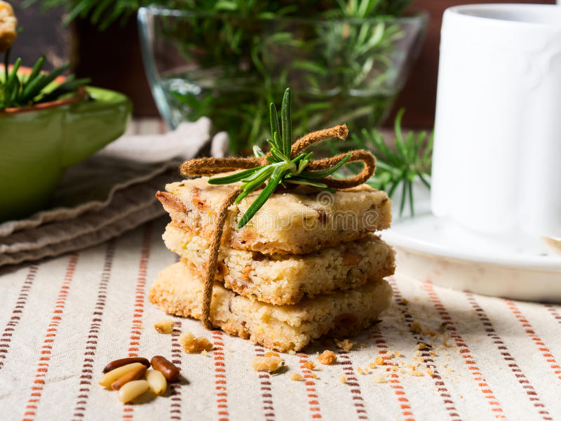 Home made cookies with rosemary and pignoli nuts. Home made butter cookies with rosemary, pignoli and pistachio nuts on table cloth with rosemary sprigs and a royalty free stock image
