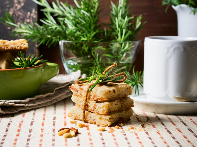 Home made cookies with rosemary and pignoli nuts. Home made butter cookies with rosemary, pignoli and pistachio nuts on table cloth with rosemary sprigs and a royalty free stock photo