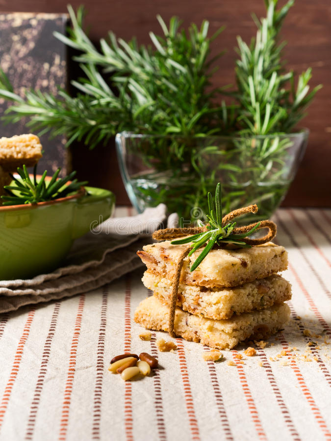 Home made cookies with rosemary and pignoli nuts. Home made stacked butter cookies with rosemary, pignoli and pistachio nuts on table cloth with rosemary sprigs stock image