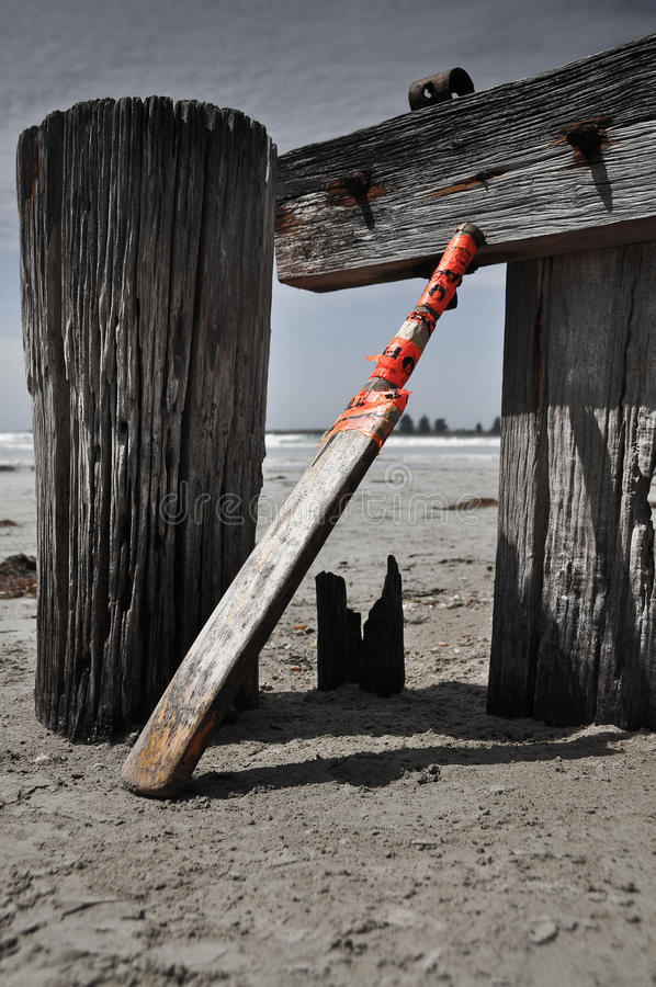 Home made cricket bat on the beach. Home made cricket bat sits unused on the beach royalty free stock images