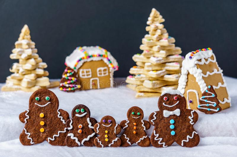 Home made delicious traditional gingerbread village and gingerbread man family black background. Home made delicious traditional gingerbread village and royalty free stock photo