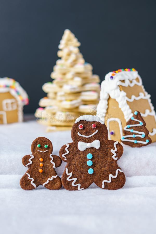 Home made delicious traditional gingerbread village and gingerbread man family black background. Home made delicious traditional gingerbread village and royalty free stock photos