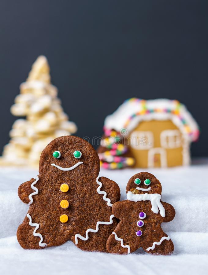 Home made delicious traditional gingerbread village and gingerbread man family black background. Home made delicious traditional gingerbread village and stock photos
