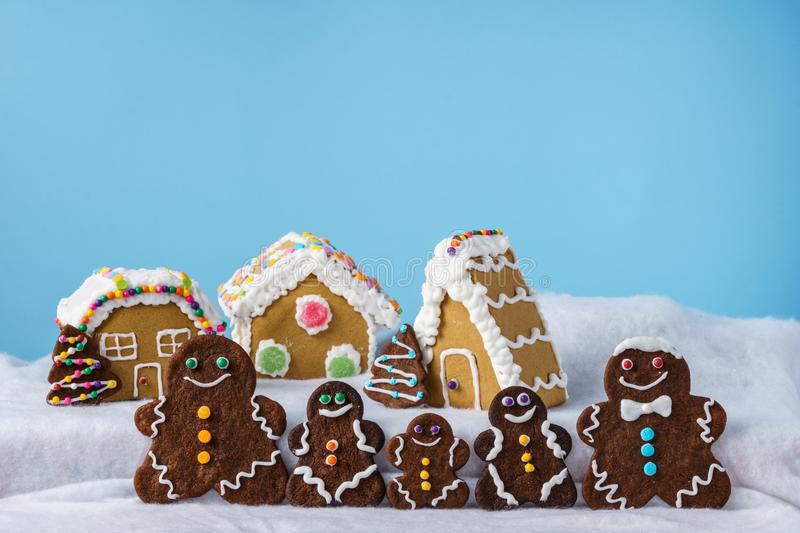 Home made delicious traditional gingerbread village and gingerbread man family blue background. Home made delicious traditional gingerbread village and royalty free stock photos