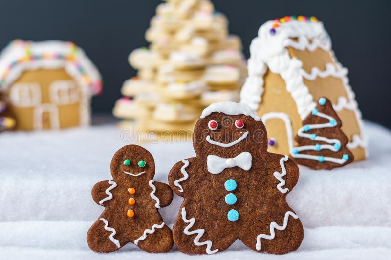 Home made delicious traditional gingerbread village and gingerbread man family black background. Home made delicious traditional gingerbread village and stock photo