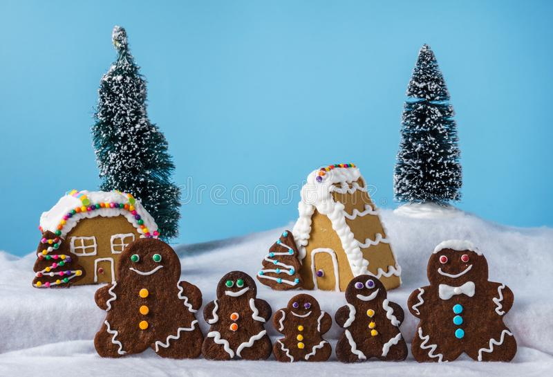 Home made delicious traditional gingerbread village and gingerbread man family blue background. Home made delicious traditional gingerbread village and stock photos
