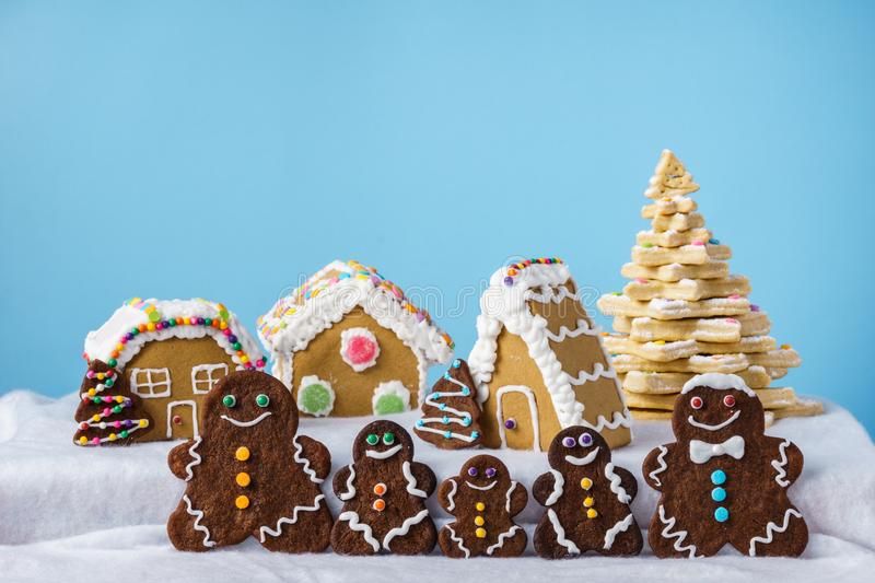Home made delicious traditional gingerbread village and gingerbread man family blue background. Home made delicious traditional gingerbread village and royalty free stock photo