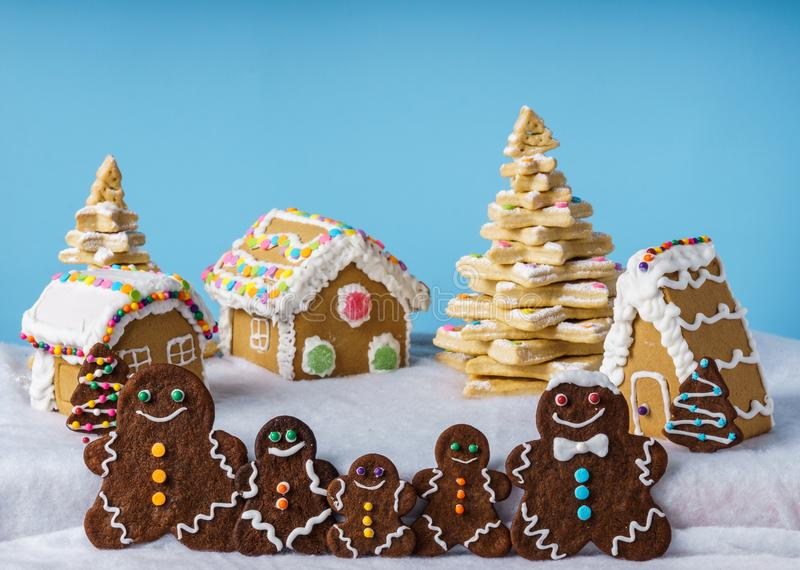 Home made delicious traditional gingerbread village and gingerbread man family blue background. Home made delicious traditional gingerbread village and stock photography