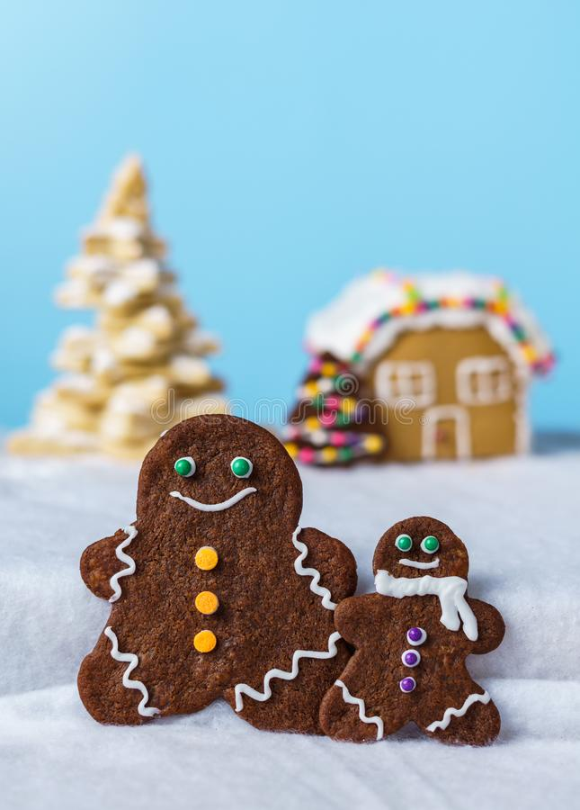 Home made delicious traditional gingerbread village and gingerbread man family blue background. Home made delicious traditional gingerbread village and royalty free stock image