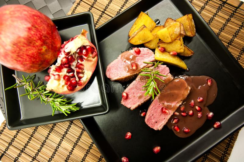 Duck breast with pomegranate, potatoes and rosemary royalty free stock photo