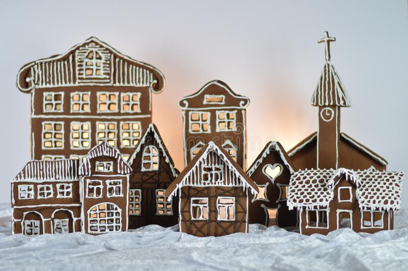 Home made gingerbread village with green background. Home made gingerbread village in front of green background on white snowlike velvet royalty free stock photography