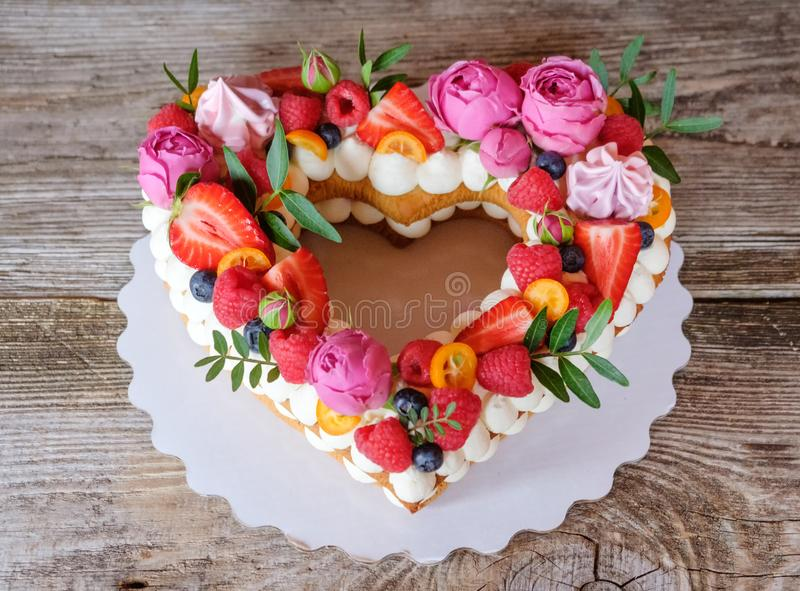 Home made heart shaped wedding cake. Beautiful homemade wedding cake in the shape of a heart , decorated with flowers and berries royalty free stock image