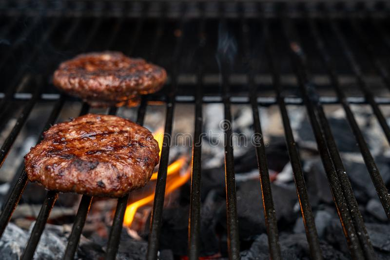 Home-made juicy beef burgers grilled on the barbecue. Fire from the charcoal beneath the hamburger. Copy space for text stock image
