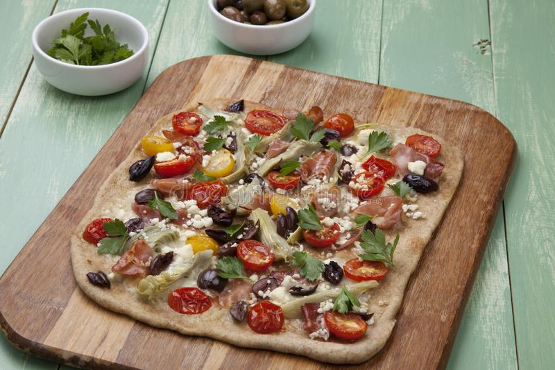 Home Made Mediterranean Prosciutto Flatbread. Closeup of home made Mediterranean flatbread made with prosciutto, artichoke, cherry tomatoes, feta cheese, and stock image