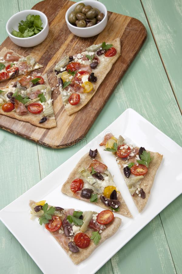 Home Made Mediterranean Prosciutto Flatbread. Closeup of a plate with few pieces of home made Mediterranean flatbread made with prosciutto, artichoke, cherry stock photo