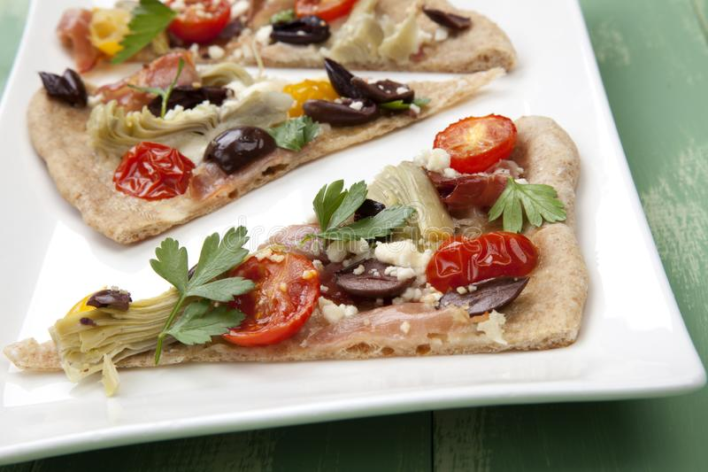 Home Made Mediterranean Prosciutto Flatbread. Closeup of a plate with few pieces of home made Mediterranean flatbread made with prosciutto, artichoke, cherry stock images
