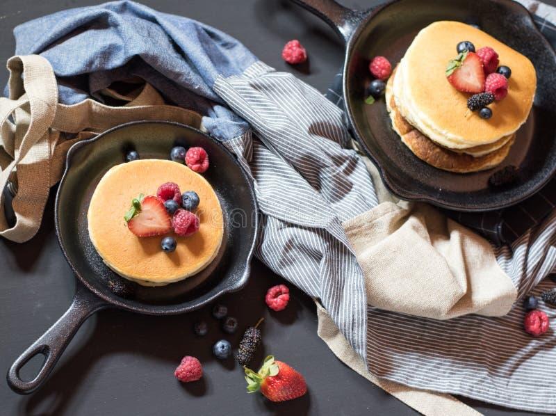 Home made pancakes with berries on metal frying pan decorated wi. Th berries blueberries, raspberries and blackberries. Top View stock image