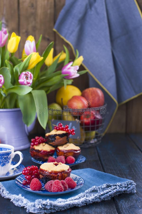 Home-made pastries with red currants and raspberries. Cupcakes for breakfast. A bouquet of spring flowers. Tulips yellow and red. stock photography