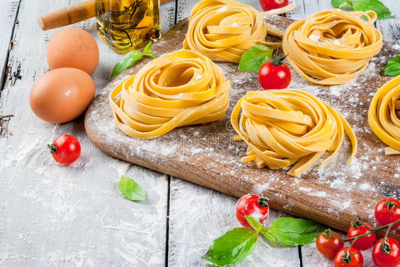 Home made raw uncooked pasta. With basil leaves, scented oil and cherry tomatoes. On a white rustic wooden table, copy space royalty free stock photos