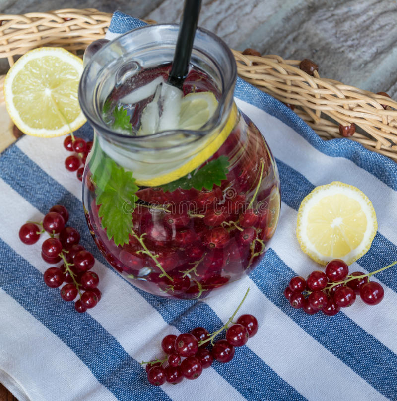 Home-made refreshing lemonade of red currant with ice and lemon royalty free stock photo