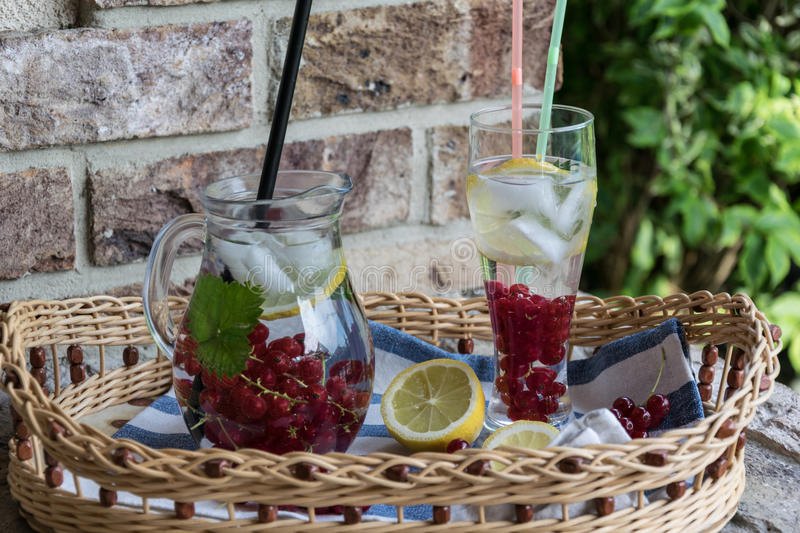 Home-made refreshing lemonade of red currant with ice and lemon stock photo