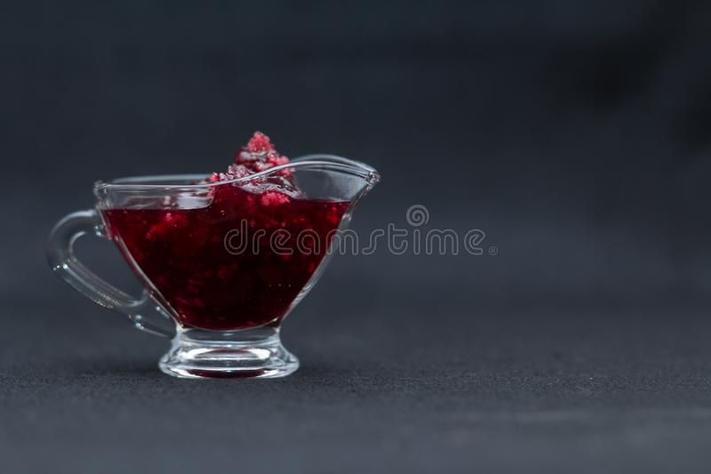 Home-made sweet raspberry jam in a glass sauce-boat on a black background. Dark food photo style stock photos