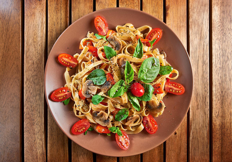 Home made vegan pasta with mushrooms, tomatoes and basil royalty free stock image