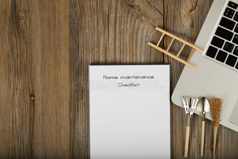 Home maintenance checklist. Gardening tools close to the laptop royalty free stock images
