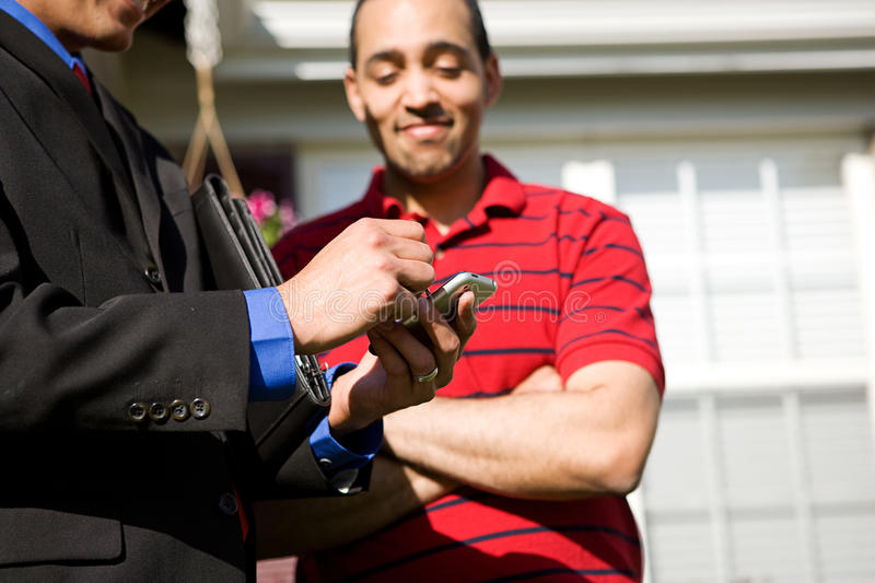 Home: Man Uses Cel Phone To Get Home Information. Extensive series of a Caucasian Real Estate Agent and African-American Couple in front of a home royalty free stock photo