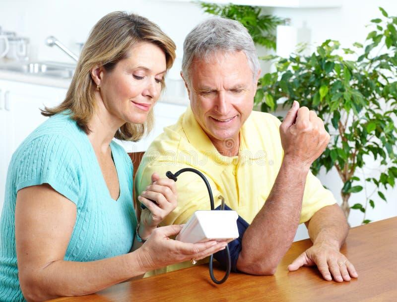 Home monitoring of blood pressure. Seniors couple at home measuring blood pressure. Home monitoring royalty free stock photo