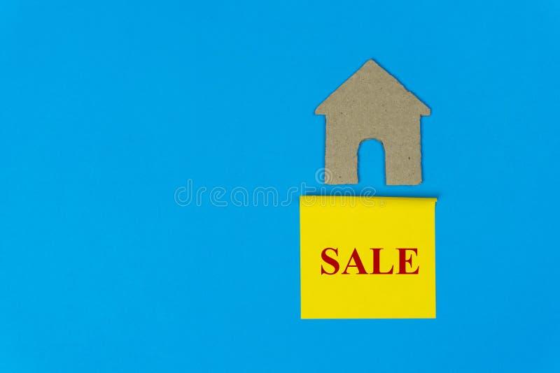 home new Egenskapsförsäljningsbegrepp Fastighetförsäljningstecken under ett litet hus som göras av det pappers- snittet på blå ba arkivfoto