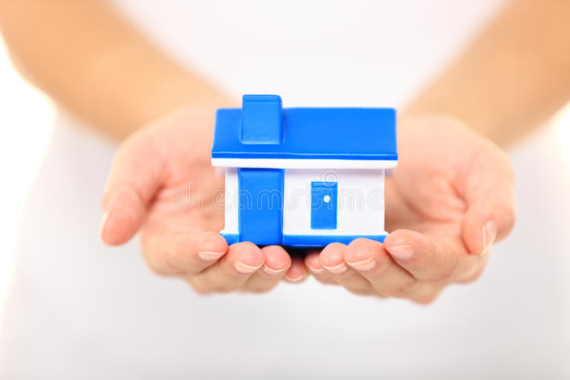 Home - new house concept. Woman holding model house stock photography