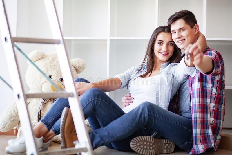 home nytt Roliga barnpar tycker om och fira att flytta sig till det nya hemmet Lyckliga par på tomt rum av det nya hemmet royaltyfri foto
