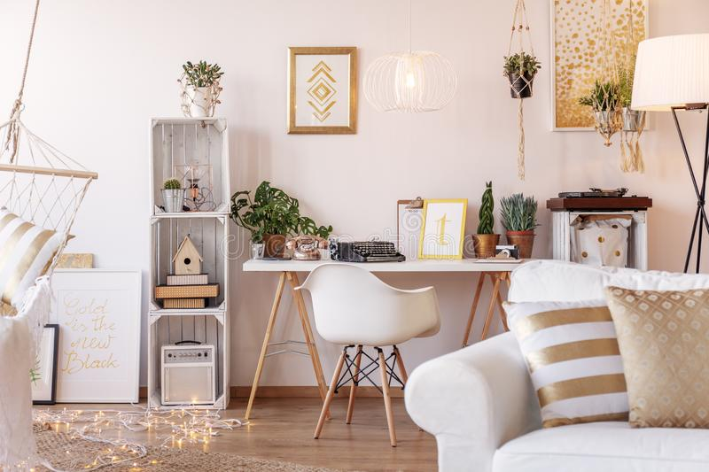 Home office desk with oldschool telephone, typewriter and fresh plants placed in white living room interior stock photos