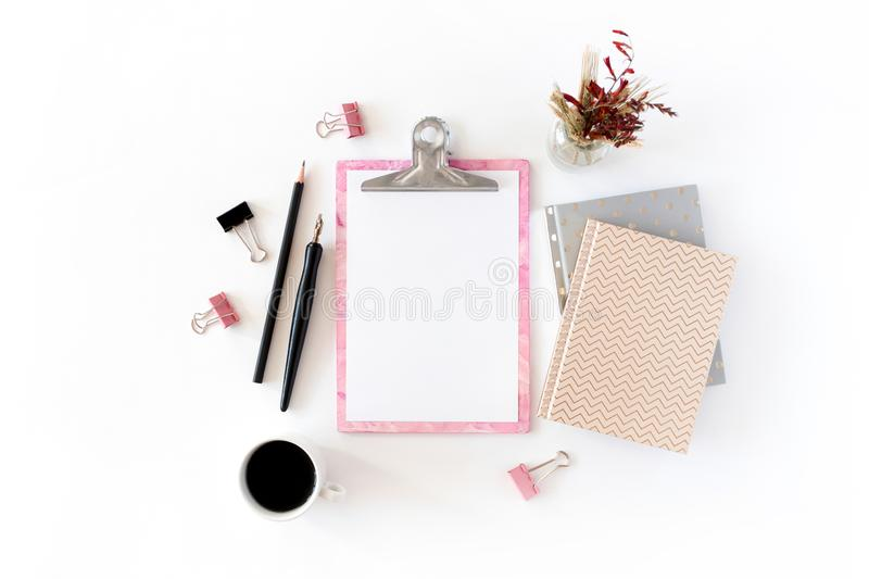 Home office desk with pink clipboard, notepads, bouquet of dry flowers, calligraphic pen, pencil, paper clips, mug of coffee royalty free stock photos