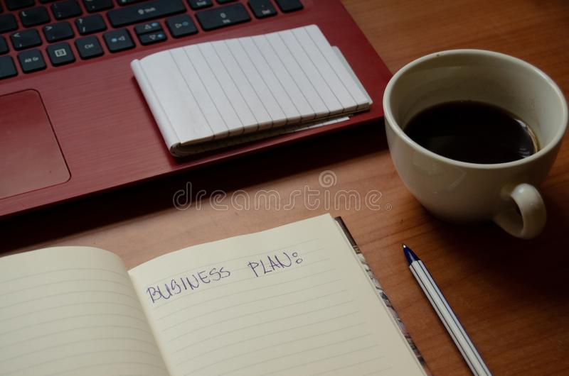 Home office desk, red laptop, coffee, notebooks, diary, pen royalty free stock photography