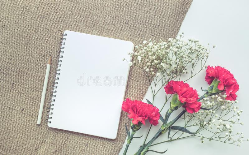 Home office desk table with notepad,flower bouquet on sackcloth stock images