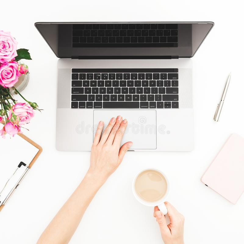 Home office desk. Woman workspace with female hands, laptop, pink roses bouquet, and diary on white background. Flat lay. Top view stock photos