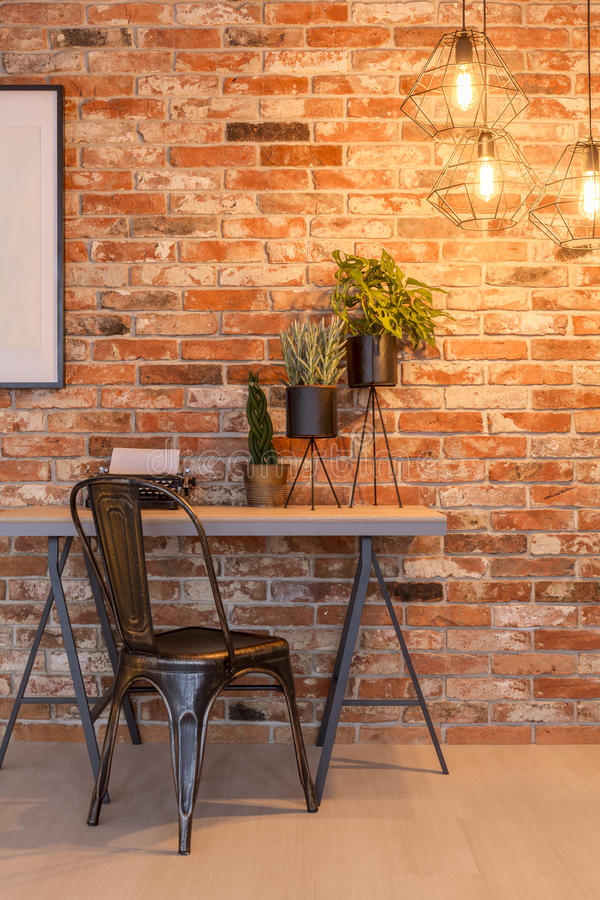 Home office in industrial style. Simple home office with industrial with brick wall, chair, desk stock photos