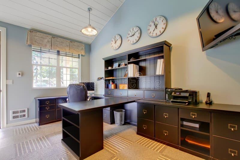 Home Office moderne bleu avec des meubles de brun foncé. photos libres de droits