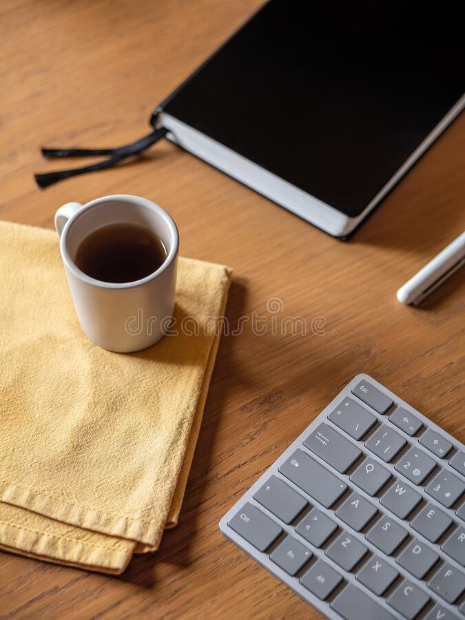Free Home Office Setup, During Self-isolation. Keyboard, Notebook, Pen, Small Cup Of Tea Or Coffee On Wooden Table Royalty Free Stock Photos - 180233728