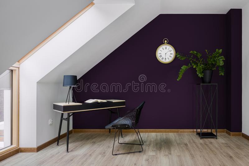 Home office with violet wall. Attic home office with violet wall, big window, stylish desk with chair royalty free stock photo