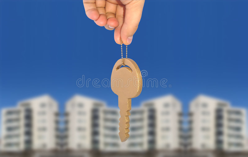 Home ownership concept. A hand holding the key to a new home. Metaphor for buying new real estate royalty free stock image