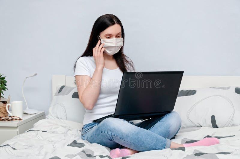 Home page do trabalho ou aprendizado on-line à distância no Quarantune Mulher na máscara remota na cama usando laptop fotos de stock royalty free
